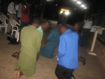 Pitana kneels to pray with those receiving Jesus